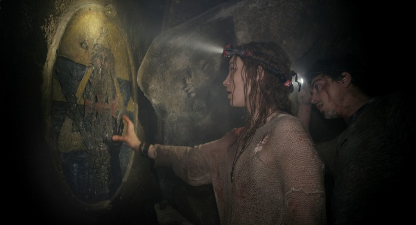 Scarlett (PERDITA WEEKS) investigates the twisting catacombs beneath the streets of Paris in As Above/So Below.