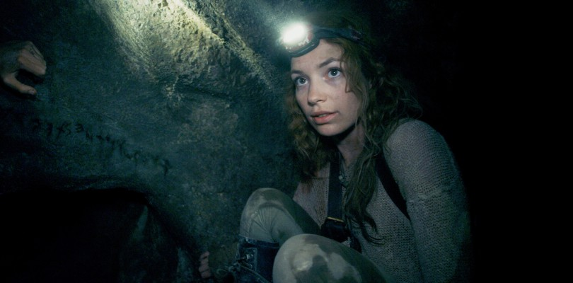 Scarlett (PERDITA WEEKS) traverses miles of twisting catacombs beneath the streets of Paris in As Above/So Below.
